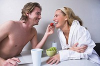 young couple sitting at table together man feeding woman strawberry