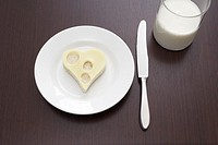 still life of cheese sandwich cut out in shape of heart on plate and glass of milk