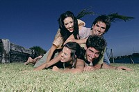 Young men and women lying on grass, smiling