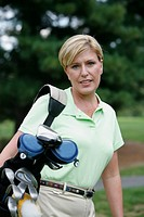Mature woman carrying golf clubs, portrait