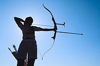 Silhouette of archer drawing back bow, low angle view