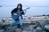 Mature woman sitting by sea, playing guitar