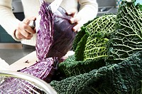 Close-up of a cabbage with a woman cutting a cabbage in the background