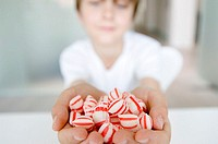 Close-up of a boy holding handful of candy