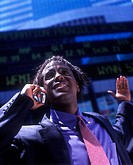 Office worker with telephone, Below stock market ticker display