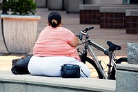 Overweight female sitting next to bicycle