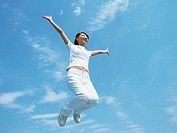 Young woman jumping up in field