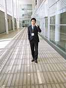Businessman on cell-phone in corridor