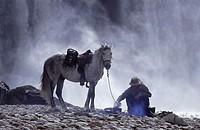 Man with horse near campfire on landscape, Mexico