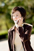 Portrait of a Mature, Smiling Woman Talking on a Cellular Phone, Front View, Differential Focus, Waist Up