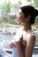 A Smiling Mid Adult Woman Standing at the Outdoor Hot Spring Bath, Side View