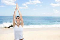 A woman exercising on a beach with hands raised