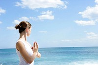 A woman meditating on a beach with joined hands