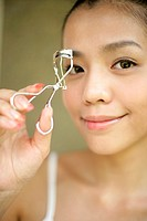 View of a young woman with an eyelash curler