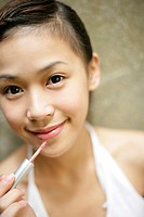Portrait of a young woman holding lip liner and smiling