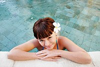 Portrait of a teenage girl leaning by swimming pool