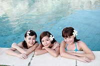 Portrait of three teenage girls leaning by a swimming pool