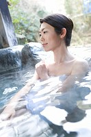 Woman in a hot tub, side view, Japan