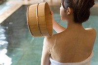 Woman pouring water on her shoulder with wooden tub, rear view, Japan