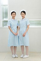 Portrait of two nurses, twin sisters, smiling and looking at camera, front view