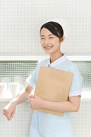 Portrait of a nurse holding a clipboard, smiling, front view