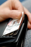 Close-up of a person's hand taking a credit card out of a wallet