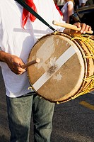 Mid section view of a man playing a drum with sticks