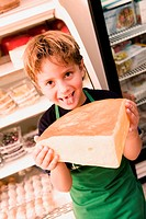 Portrait of a boy holding cheese and sticking his tongue out