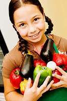 Portrait of a girl holding vegetables and smiling