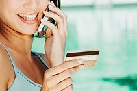 Close-up of a young woman holding a credit card and talking on a mobile phone