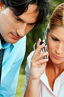 Close-up of a businesswoman and a businessman using a mobile phone