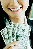 Close-up of a businesswoman holding American dollar bills and smiling