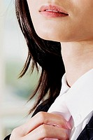 Close-up of a businesswoman adjusting her tie