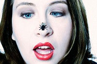 This stock photo shows an attractive young woman, age 20_25, looking with crossed blue eyes at a plastic fly on her nose.