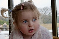 3 year old girl looking off camera, a serious expression, with huge blue eyes
