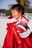 Side profile of a girl in traditional clothing smiling
