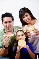 Young woman and a mid adult man with their daughter holding slices of fruits and sticking their tongues out