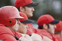 Baseball players looking on from the dugout