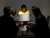 Businesswoman With Colleagues Sitting in a Dark Office Opening a Bright Briefcase