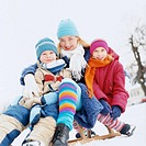 Mother With Two Children Sitting Outdoors on a Sled in the Snow