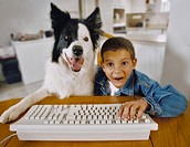 Excited Young Boy and His Border Collie Sitting at a Table, Boy Using Keyboard