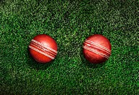 New and old cricket ball on grass, elevated view, digital composite