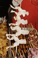 Frog legs on skewers at market stall, close-up