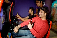 Young men in amusement arcade playing video games