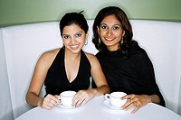 Two women sitting side by side, having tea, looking at camera