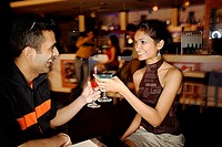 Couple in a club, toasting with cocktails