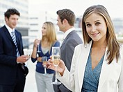 Businesswoman having champagne, smiling, colleagues in background