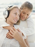 Daughter 9-11 embracing mother wearing headphones, smiling, close-up