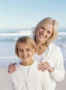 Mother and daughter 10-12 standing on beach, smiling, portrait