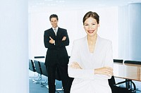 Businesswoman and businessman in meeting room, smiling, portrait